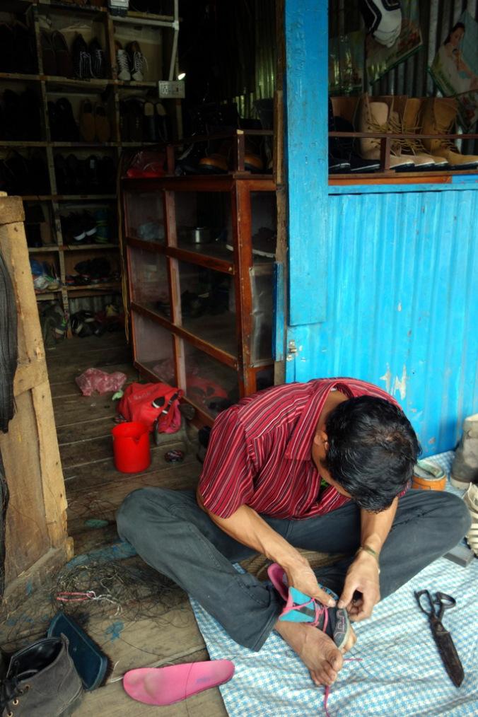 Getting my shoe fixed in Kamdeme.