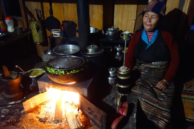 Tibetan woman in the kitchen drinking Tongba